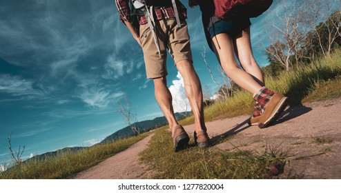 Closeup legs Hiking couple asian walk trekking travel together at forest for camping with backpack on holidays weekend near river and mountain view.