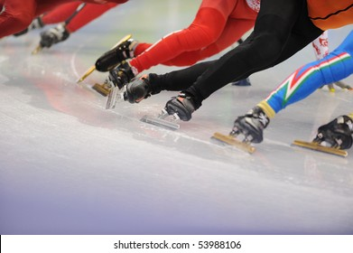 A close-up of the legs of ice-skaters in a race.