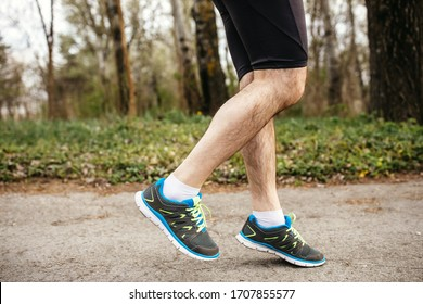 Close-up of legs of a man running in the morning on park or forest path. Healthy active man jogging.