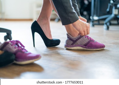 Close-up of legs of an office female employee with foot pain. A woman changes high black suede heels to more comfortable shoes. The girl takes off her shoes and puts on purple running shoes.