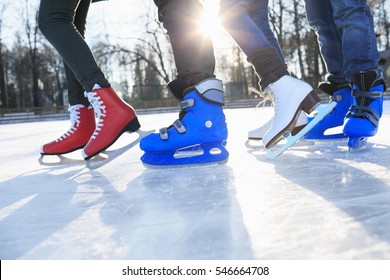 Closeup of legs in skates on ice rink.  Friends skating together outdoors  at winter frozen lake