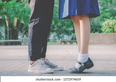 Closeup legs and sneakers of couple in school uniform standing in the park, Symbol sign couple embracing kissing. Lovers spend time together on romantic date. First teens love and amorousness concept