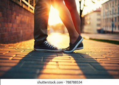 Closeup of legs and sneakers of young beautiful couple in love standing on the street in summer evening