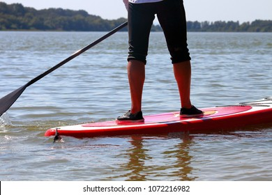 Closeup of legs standing on SUP board. Paddle board man doing stand-up paddleboard on river. Athlete paddleboarding on SUP surf board.