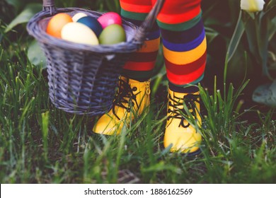 Close-up of legs of toddler girl with colorful stockings and shoes and basket with colored eggs. Child having fun with traditional Easter eggs hunt, outdoors. Celebration of christian holiday.