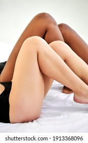 close-up legs of two diverse women, cropped female posing at camera, soft black and white skin together. african and caucasian half-naked women