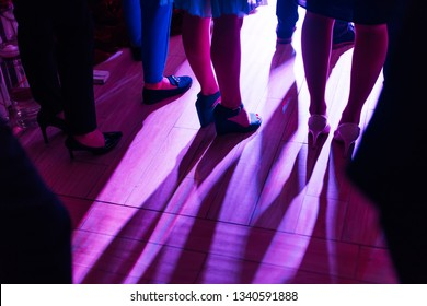 A close-up of the legs of the wedding guests. wedding hall with color lighting