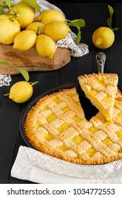 Close-up of lemon pie with a slice cut and fresh lemons.