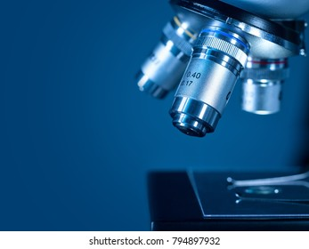 Closeup lens of a modern microscope in a research lab on a dark blue background. High resolution studio image.