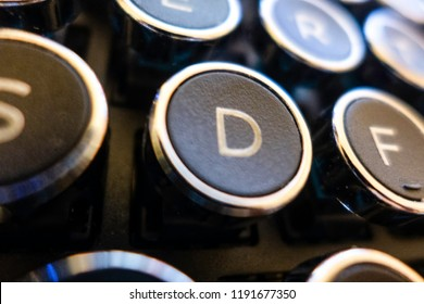 A close-up of the letter D key in an old-style typewriter QWERTY keyboard.
