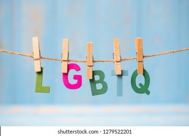 closeup LGBTQ text, for lesbian, gay, bisexual, transgender, and queer hanging on line with blue wooden background