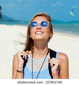 Closeup lifestyle fashion portrait of pretty young beautiful blonde smiling woman in blue sunglasses having fun outdoor in summer on vacation in windy sunny weather on the beach