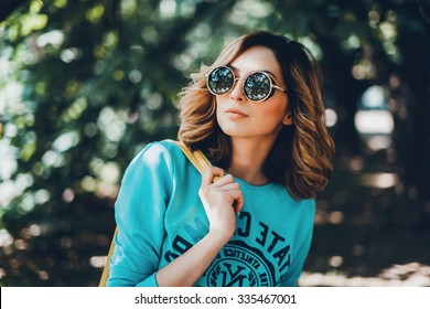 Close-up lifestyle fashion portrait of young hipster woman walking at park , travel with backpack, stylish casual outfit, evening sunset, reflecting sunglasses student, bright make up bf hairstyle