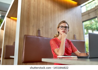Closeup lifestyle portrait of young pensive blonde caucasian millennial blogger wearing glasses taking notes on a laptop in a bright trendy restaurant