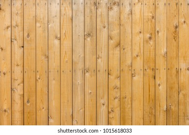 Closeup of light brown wooden wall or floor. It is made of hardwood lumber.
