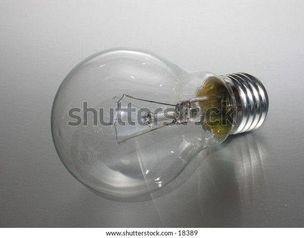 Closeup of a light bulb on a gray background.