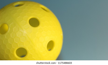 Close-up of light green floorball ball in light blue background with copy space.