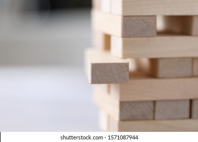 Close-up of light wooden tower made of blocks. One brick lay uneven. Board game jenga on table. Activity for strategy and concentration. Business concept