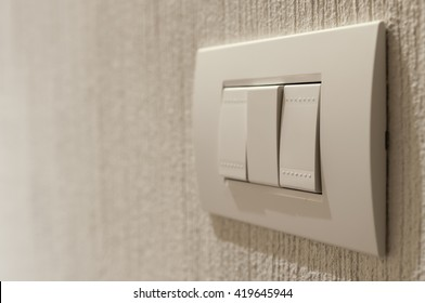 Closeup of  a lighting switch on concrete wallpaper background with copy space.