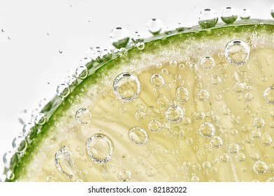 Closeup of lime slice with soda in glass