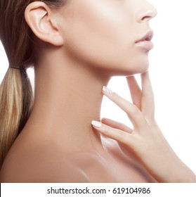 Close-up lips and hand of beautiful woman over white background touching her neck. Sexy lips with natural beige lipstick makeup