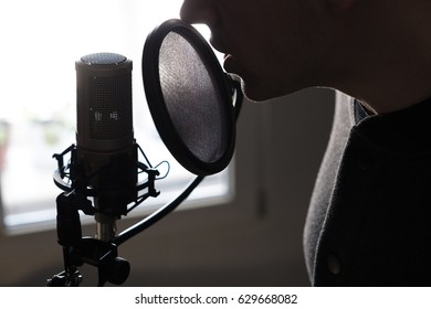 A closeup of lips at the microphone of a young man standing in profile, horizontal photo