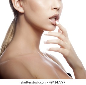 Close-up lips and shoulders of young caucasian girl with natural make-up, perfect skin touching her lips isolated on white background. Studio portrait.
