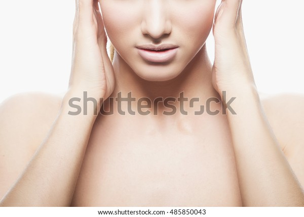 Close-up lips and shoulders of young caucasian brunette woman with natural lips, make-up and blue eyes isolated on white. Touch her head. Perfect skin. Studio portrait.