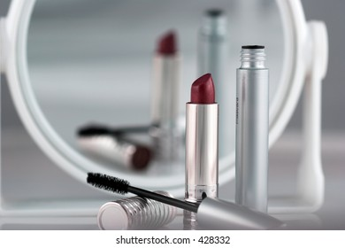 Closeup of lipstick and mascara with a blurred reflection in a makeup mirror.  Could be used as a metaphor for beauty.