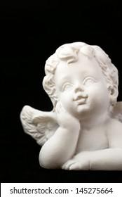 Close-up of little angel on black background