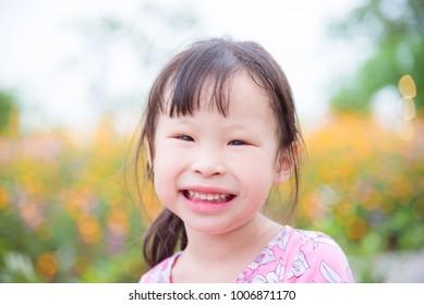 Closeup of little asian girl smiling at camera in flower garden