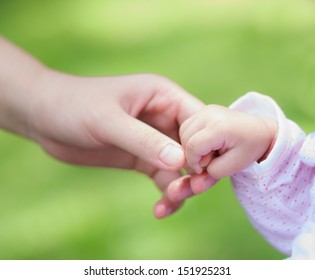 closeup little baby holding mother's hand