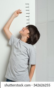 Closeup of little boy measuring height himself against white wall. Smiling cute boy measures his height. Boy growing tall. Young boy checking his height with the hand.