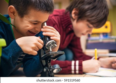 Closeup of little boy using microscope on biology lesson