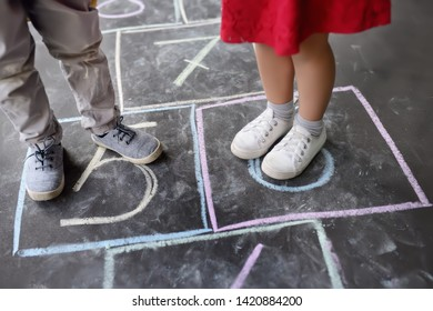 Closeup of little boy's and girl's legs and hopscotch drawn on asphalt. Child playing hopscotch game on playground outdoors on a sunny day. Summer activities for children.