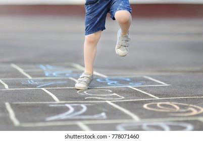 Closeup of little boy's legs and hopscotch drawn on asphalt. Child playing hopscotch game on playground outdoors on a sunny day. Summer activities for children.