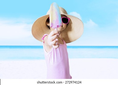 Closeup of little child with a big hat standing on the beach while wearing swimwear and showing ice cream