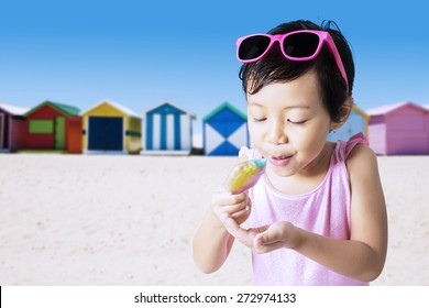 Closeup of little child eats a melt ice cream on the shore while wearing swimwear