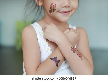 Close-up little child girl with butterfly tattoo sticker on body skin, Dress up tattoos.