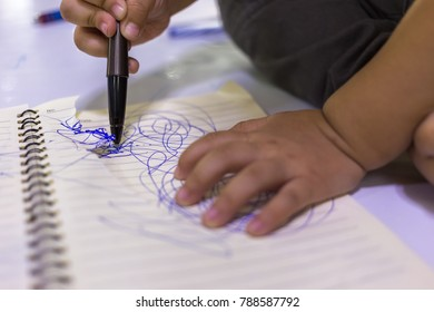 closeup of little child hands writing and drawing on book paper with blue pen
