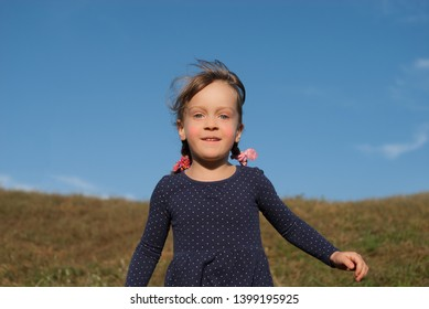 Closeup of a little four-years-old girl. Laughing happy little child outdoor. Smiling kid with beautiful blue eyes. Grass and blue sky on background. Concept - happy childhood.