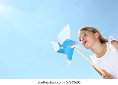 Closeup of little girl blowing blue wind wheel