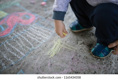 Close-up of a little girl and boy in canvas shoes with chalk on the sidewalk. a piece of chalk. draw on asphalt