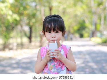 Closeup of little girl drinking milk with straw in the park. Portrait outdoor.