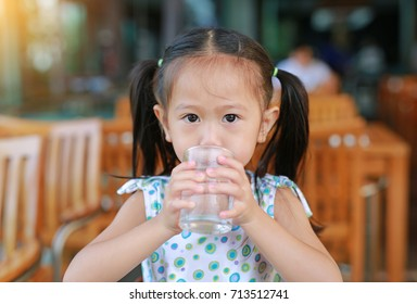 Closeup of little girl drinking a water from glass with looking at camera.