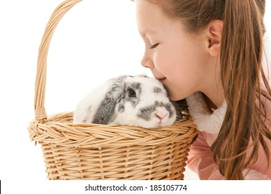 Close-up of little girl kissing bunny rabbit in basket.