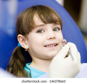 Close-up of little girl opening his mouth wide during inspection of oral cavity