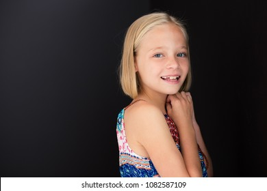 Close-up of a little girl with a smile on her face while holding her hands close to her face.