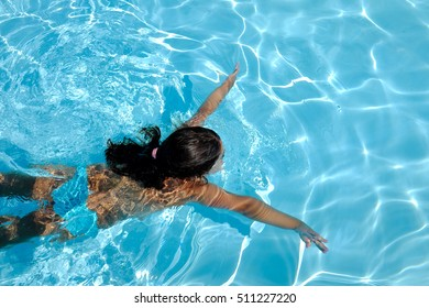 Closeup of a little girl swims in the pool as a concept of sports