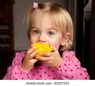 Closeup of a little girl taking a bite out of a corn on the cob